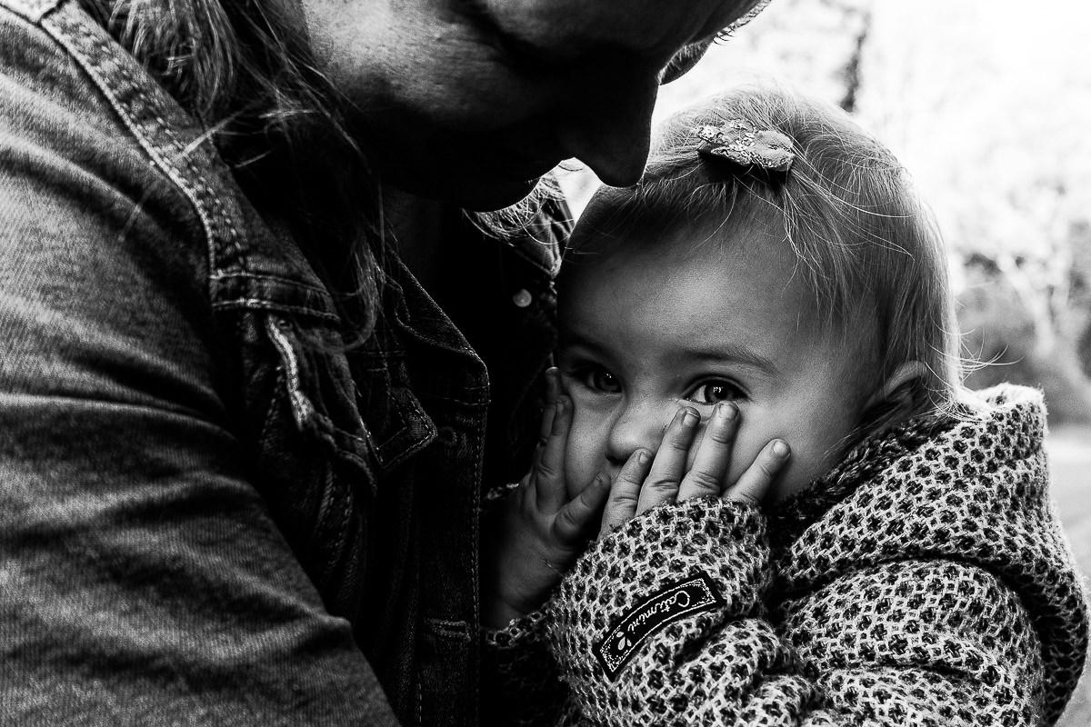 petite fille qui se cache dans les bras de sa maman
