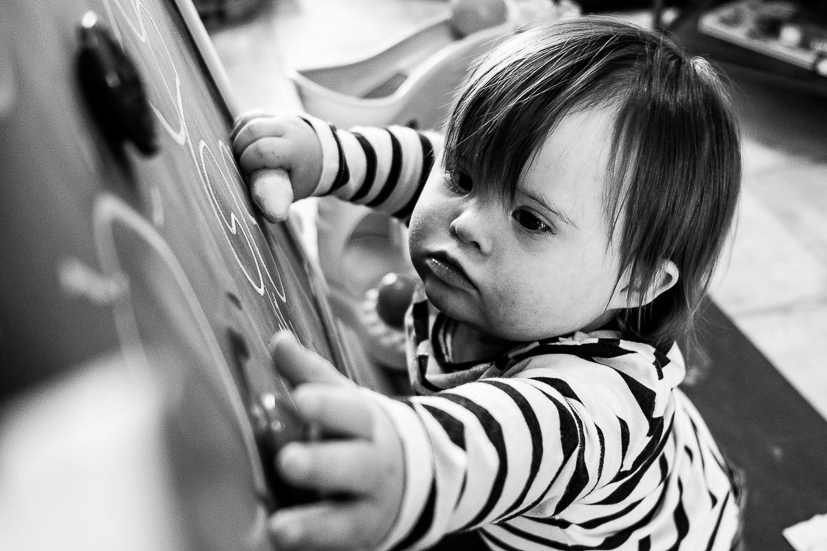 petite fille trisomie 21 joue au tableau