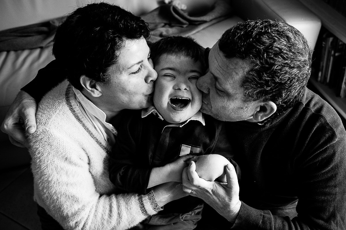 petit garçon trisomique avec ses parents qui l'embrassent
