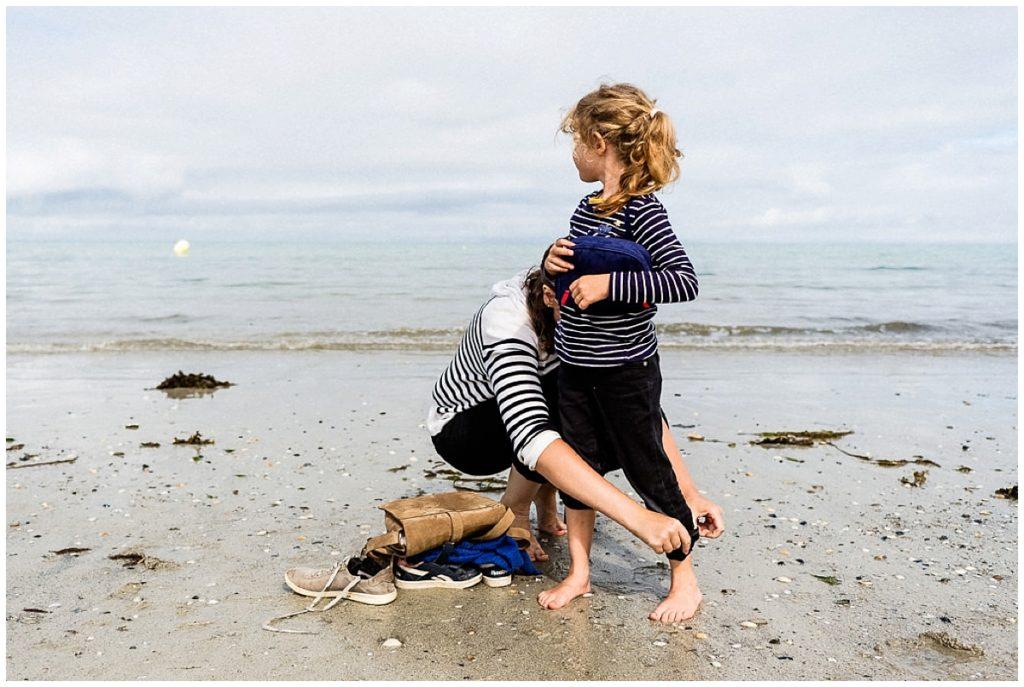 maman qui aide sa fille à retrousser son pantalon sur la plage