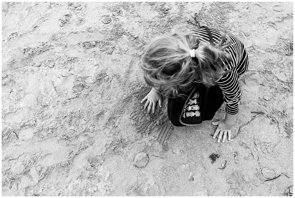 petite fille qui touche le sable