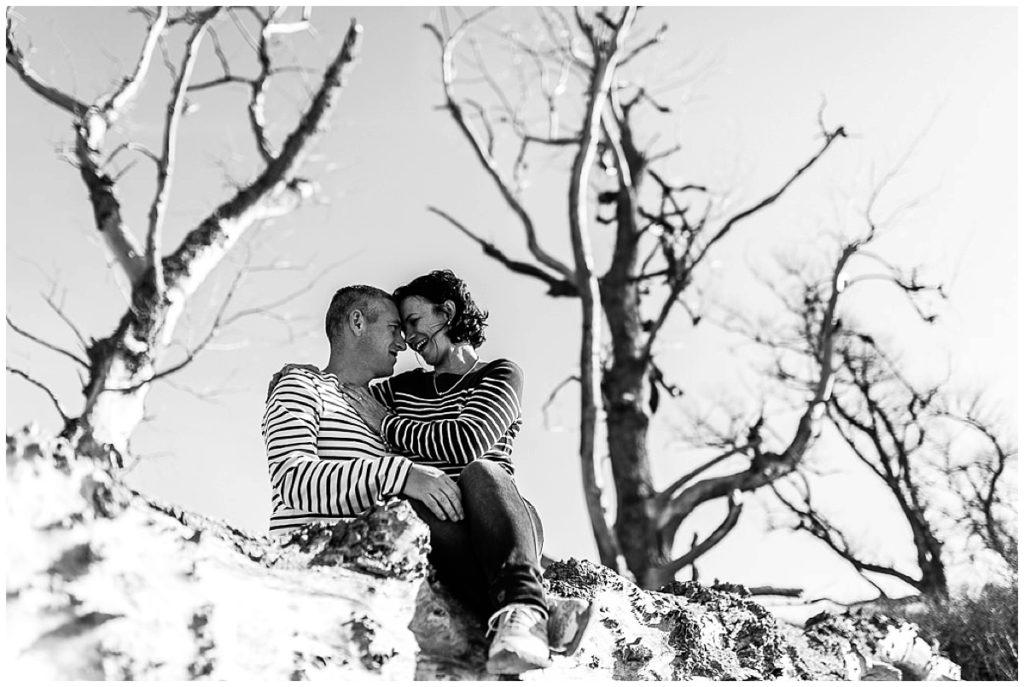 couple qui se regarde sur un tronc d'arbre