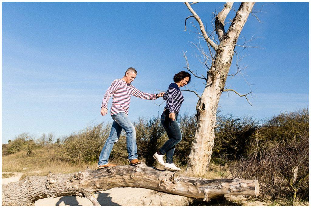 couple qui marche sur un tronc d'arbre