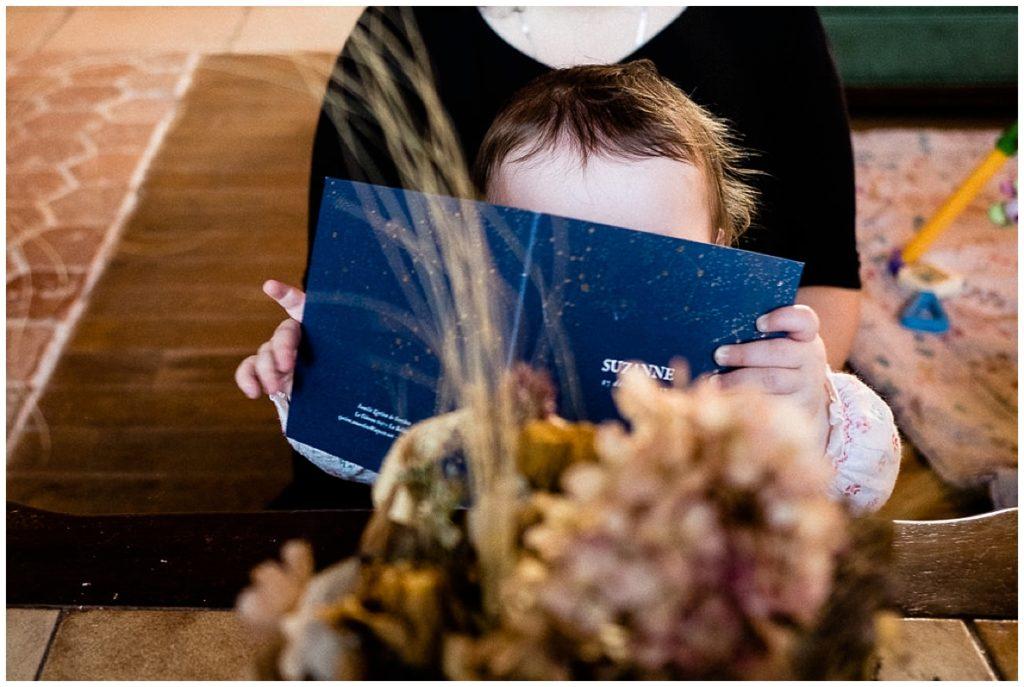 bébé qui lit son faire part de naissance