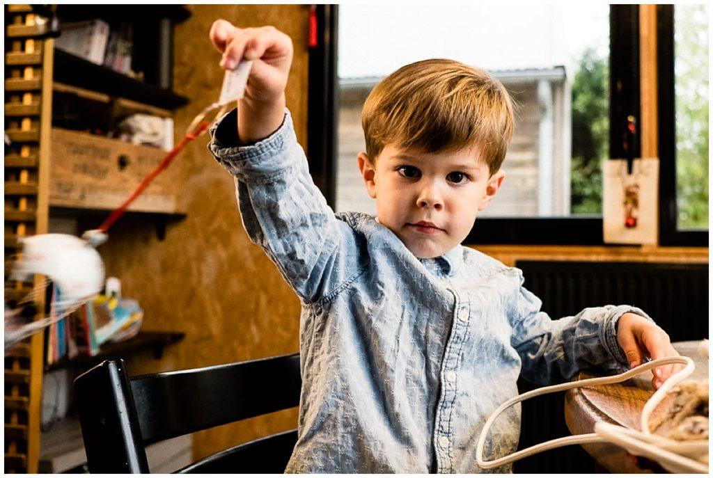 petit garçon qui joue avec une décoration de noel