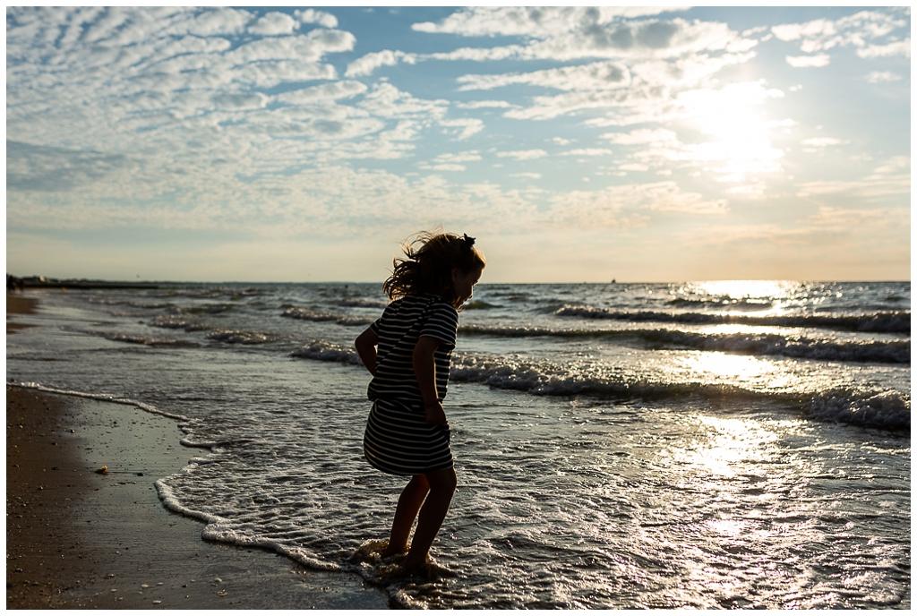 séance famille cabourg, petite fille qui saute dans la mer à cabourg