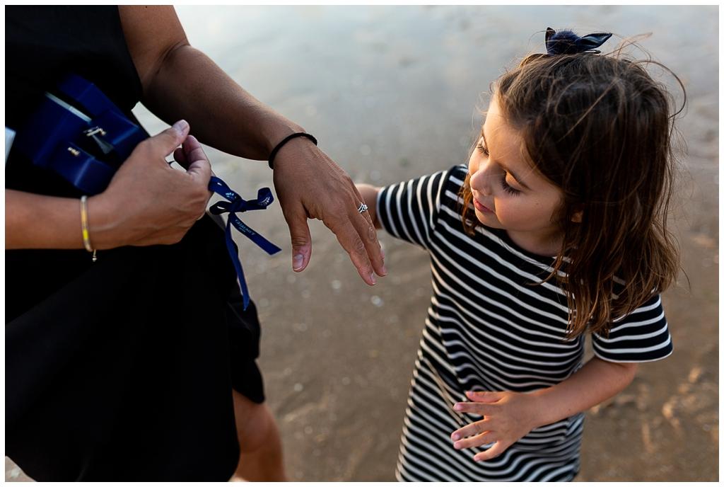 petite fille qui admire la bague de fiançailles de sa maman, audrey guyon photographe mariage en normandie