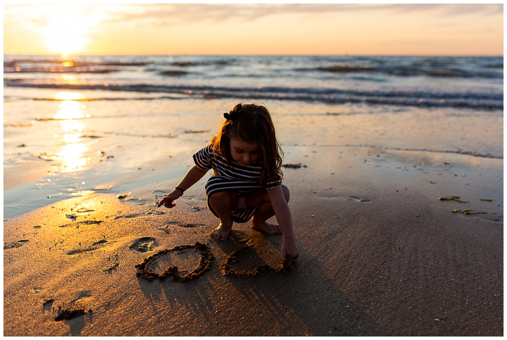 petite fille qui dessine un coeur dans le sable à la golden hour. Audrey GUYON, photographe famille normandie