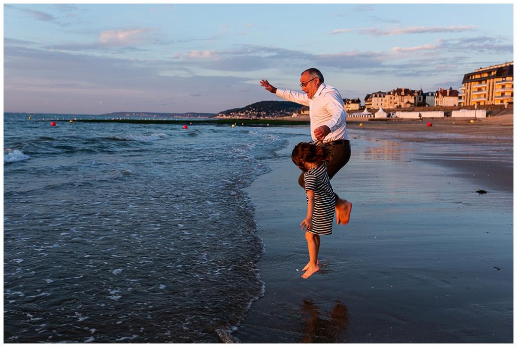 papa et sa fille qui sautent au bord des vagues à cabourg. photographe famille cabourg, audrey guyon