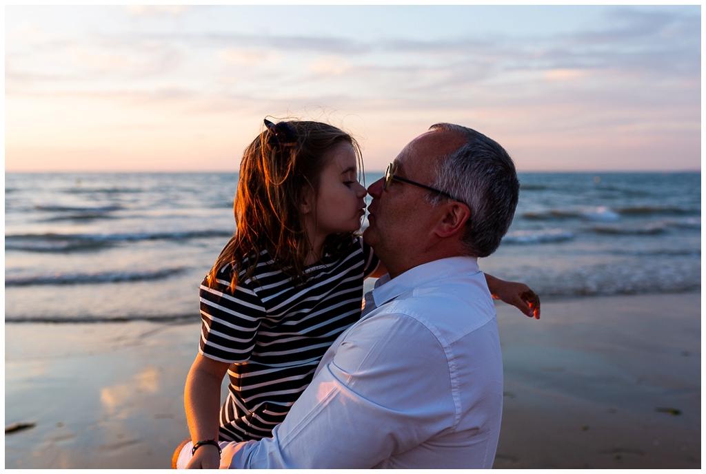 un papa et sa fille qui se font un bisou