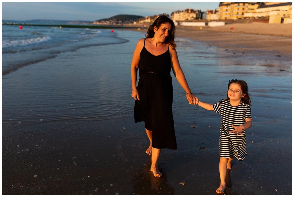 maman et sa fille qui marche main dans la main sur la plage de cabourg
