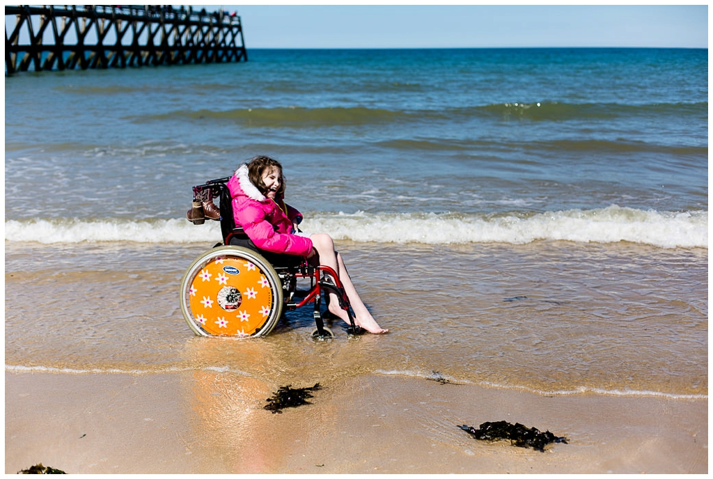 jeune fille les pieds dans l'eau avec son fauteuil roulant