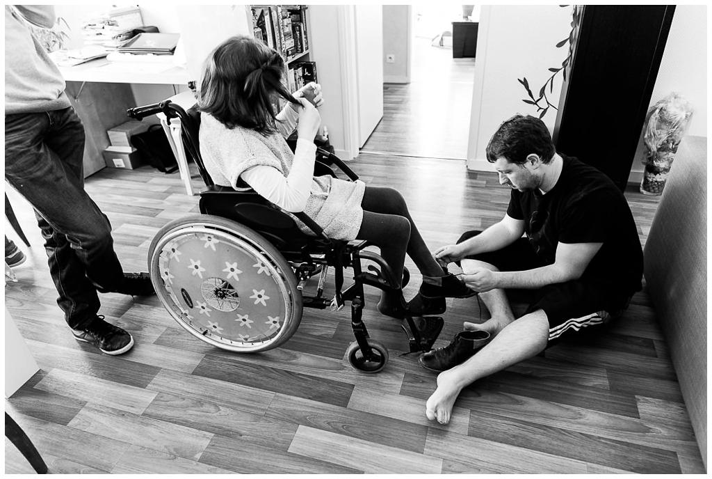 aidant familial qui lace les chaussures de son proche en situation de handicap, audrey guyon photographe du handicap
